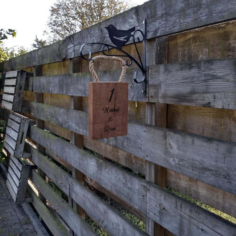 Bedrijfslogo op houten plank aan entree-deur